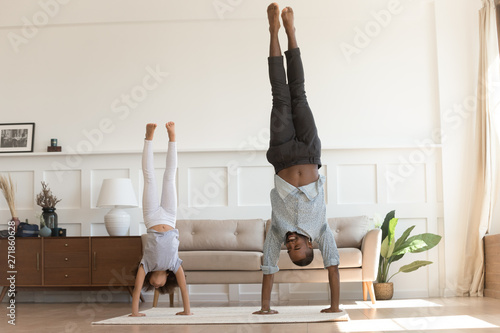Photo Active african kid girl copy father doing handstand at home