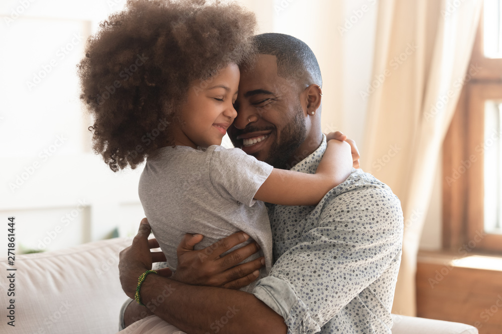 Fototapeta Happy african father holding embracing cute little child daughter