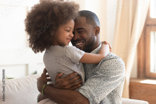 Fototapeta Happy african father holding embracing cute little child daughter obraz