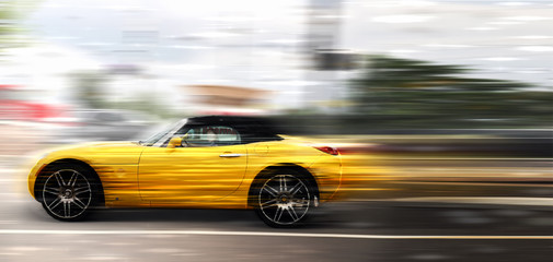 A yellow car at high speed rides along the road, speed in motion
