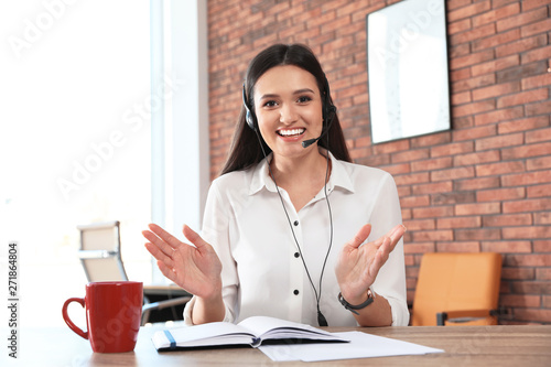 Foto Young woman with headset looking at camera and using video chat in home office