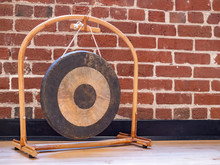 Small Suspended Gong Sitting On Wooden Floor Against Brick Wall Backdrop