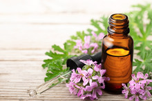 Geranium Essential Oil With Fresh Geranium Flowers, On The Old Wooden Board