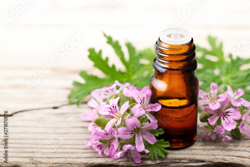 Geranium essential oil with fresh geranium flowers, on the old wooden board Wallpaper Mural