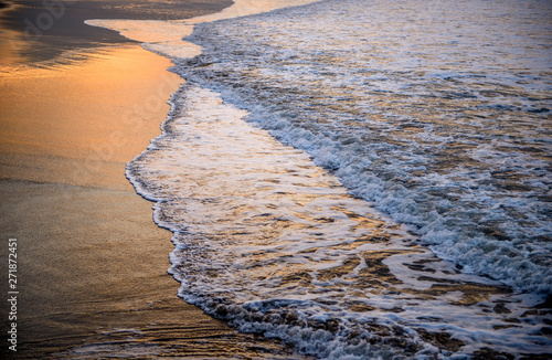 Tuinposter Lavendel Landscape of wave power, sunset view. Golden light, black sand. Long cloud beneath mountain top.