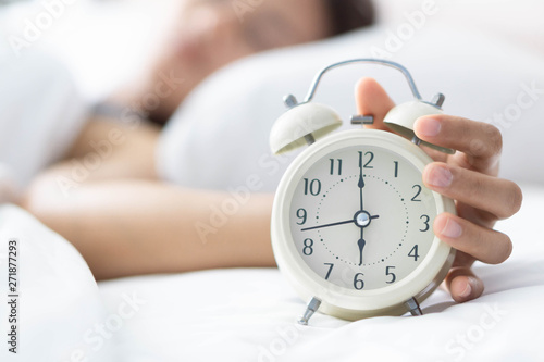 Closeup woman sleeping on bed and hand holding alarm on clock, Time to wake up
