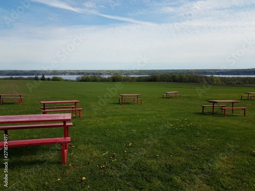 red picnic tables in green grass or field with river in Quebec, Canada