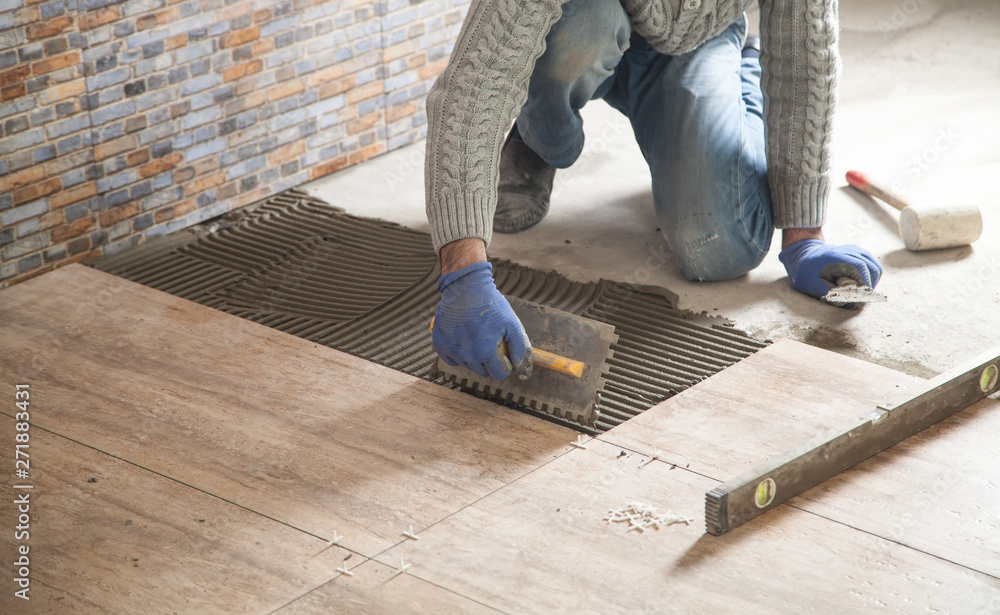 Fototapeta Laying floor ceramic tile. Renovating the floor
