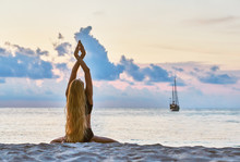 Young Caucasian Slender Woman In Swimsuit With Blonde Hair Make Yoga Exercises On A Sandy Beach At Morning