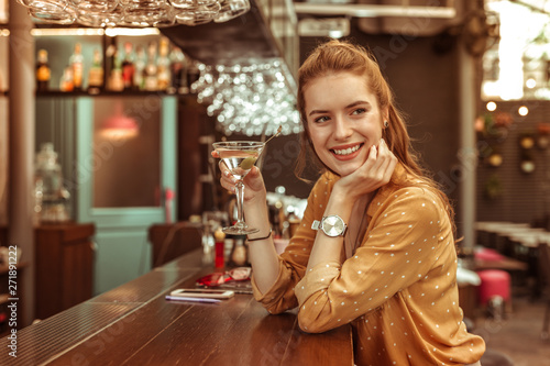 Obraz Smiling woman holding martini drink sitting at the bar counter - fototapety do salonu