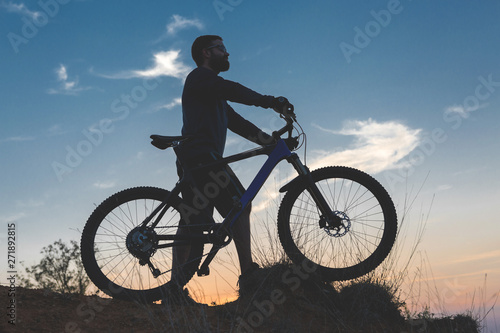 Aluminium Prints Cycling Cyclist in shorts and jersey on a modern carbon hardtail bike with an air suspension fork rides off-road on the orange-red hills at sunset evening in summer