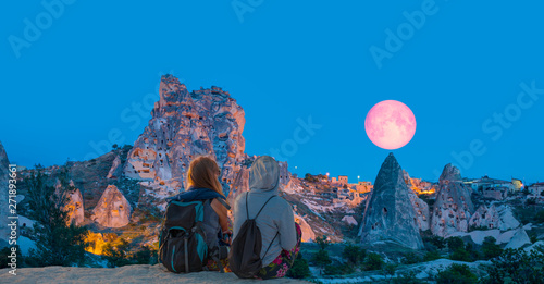 "Amazing view of Uchisar castle in Cappadocia at twilight blue hour - Girls watching moonrise at the hill of Cappadocia""Elements of this image furnished by NASA"""