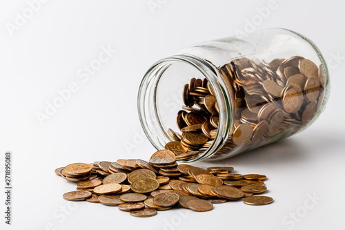 Fotografía  Gold coins spilling out of a jar on white background