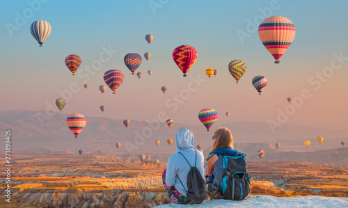 Montgolfière / Dirigeable Hot air balloon flying over spectacular Cappadocia - Girls watching hot air balloon at the hill of Cappadocia