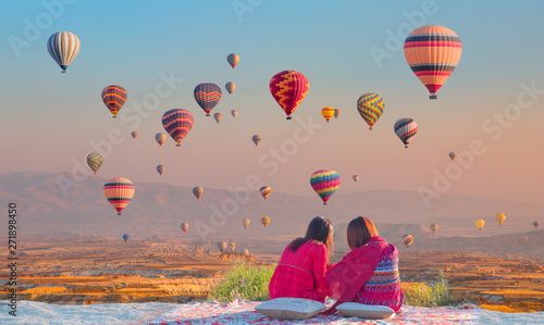 Hot air balloon flying over spectacular Cappadocia - Girls watching hot air balloon at the hill of Cappadocia