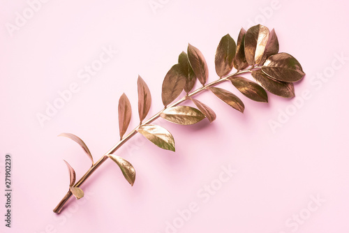 Floral minimal style concept. Exotic summer trend. Golden tropical leaves and branch on pastel pink color background. Shiny and sparkle design, fashion concept.