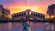 Gondolier carries tourists on gondola near Rialto Bridge - Venice, Italy