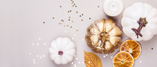 Decorative Pumpkins, Golden Confetti And Dry Leaves On Gray Background. Autumn Concept