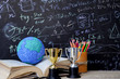 Study learning achievement success in abroad education global ideas: School books with global model on open book, gold silver trophy on desk,pencils box, formula math equation blackboard background