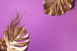 canvas print picture - Golden tropical monstera leaf on violet background with copy space. Top view. Flat lay. Creative layout. Exotic summer concept in minimal style