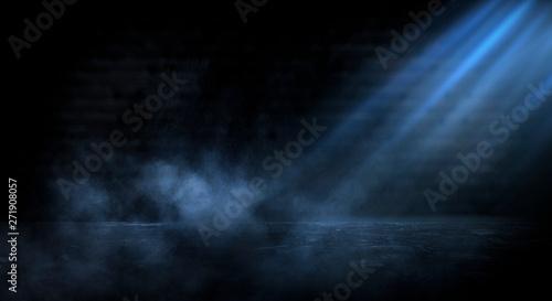 Dark empty scene, blue neon searchlight light, wet asphalt, smoke, night view, rays. Empty black studio room. Dark background. Abstract dark empty studio room texture. Product showcase spotlight back