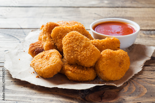 Fototapeta chicken nuggets with tomato sauce on wooden background. Copy space. obraz