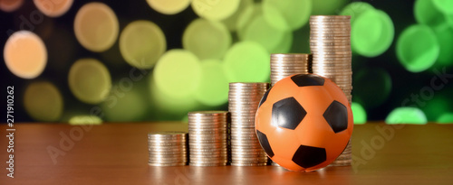 Cuadros en Lienzo Soccer ball and stacks of golden coins in growth graph on the blurred bokeh back