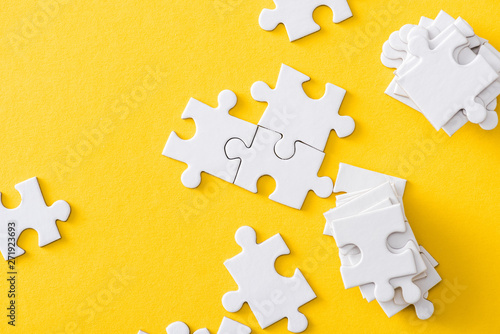 Fotografia  top view of white stack of jigsaw near connected puzzles isolated on yellow