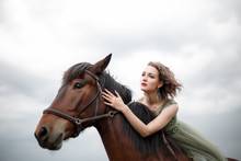Close-up Portrait Of An Independent Girl Riding A Brown Horse. Girl Looking Into The Distance