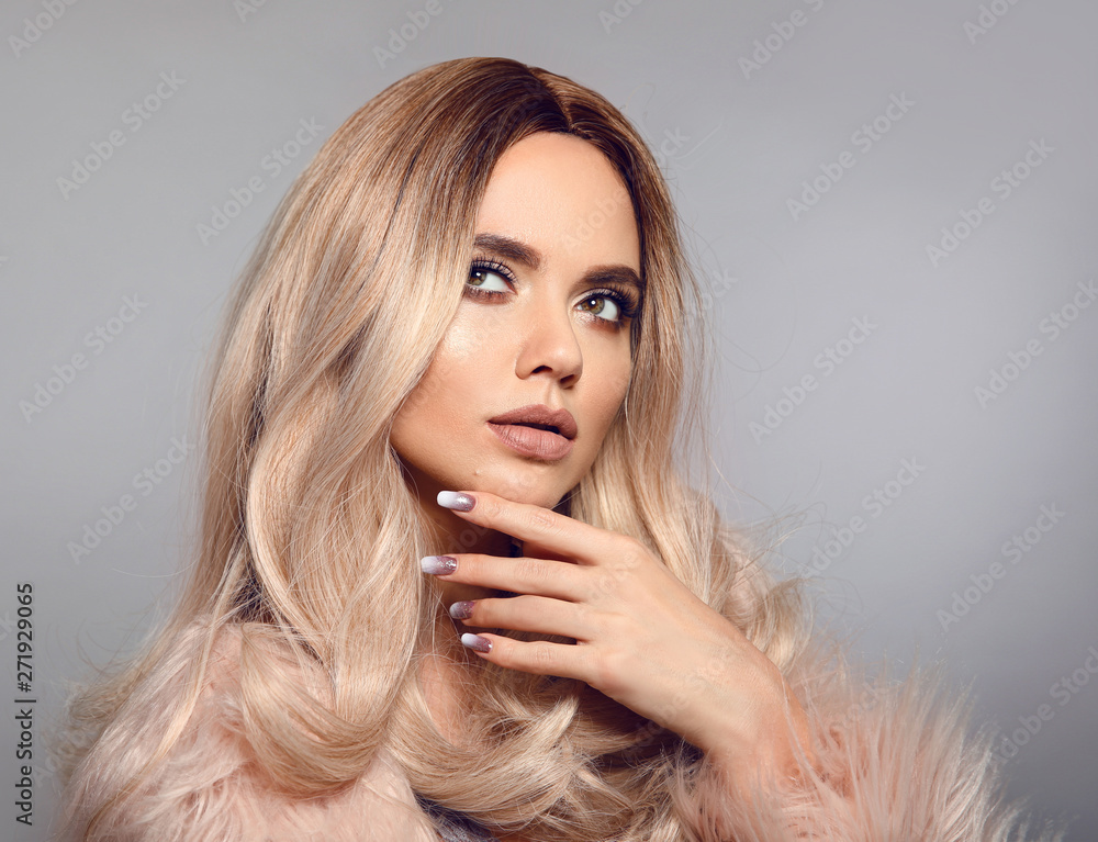 Fototapeta Blonde woman in glamorous fur coat posing in studio. Ombre blond hairstyle. Beauty fashion girl portrait. Beautiful model with makeup, long healthy hair style. Manicured nails.