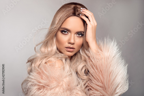Sexy woman wears in pink fur coat. Ombre blond hairstyle. Beauty fashion blonde portrait. Beautiful girl model with makeup, long healthy hair style posing isolated on studio grey background.