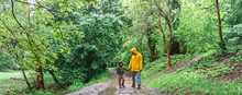 Father And Son Walking In A Rainy Day