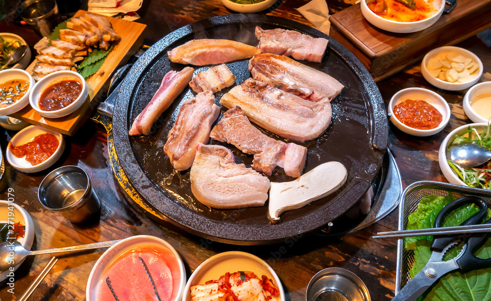 Fototapeta Pan-fried cooked black pork meal in Korea restaurant, fresh delicious korean food cuisine on iron plate with lettuce, close up, copy space, lifestyle