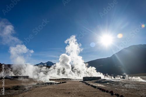 Bright rising sun above erupting Hot Geyser Of Steam in El Tatio Geysers field a Wallpaper Mural