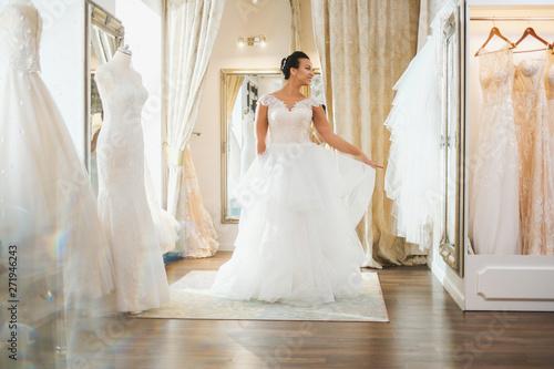 Fotomural Beautifu bride choosing wedding dress in a wedding salon