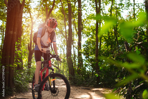 Woman cyclist bicycle riding in way of the rain forest road, adventure woman rid Wallpaper Mural