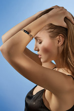 Cropped Side View Shot Of Blonde Lady, Wearing Black Crop Top And Silver Bangle Bracelet With Massive Black Onyx Gemstone. The Woman Is Fixing Hair With Eyes Closed, Standing On The Blue Background.