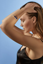 Cropped Side View Shot Of Blonde Lady, Wearing Black Crop Top And Silver Bangle Bracelet With Massive Royal Blue Gemstone. The Woman Is Fixing Hair With Eyes Closed, Standing On The Blue Background.