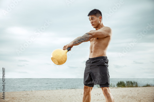 Fotografía  Young healthy man athlete doing exercise with the weight at the beach