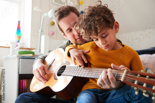 Single Father At Home With Son Teaching Him To Play Acoustic Guitar In Bedroom - 271971273