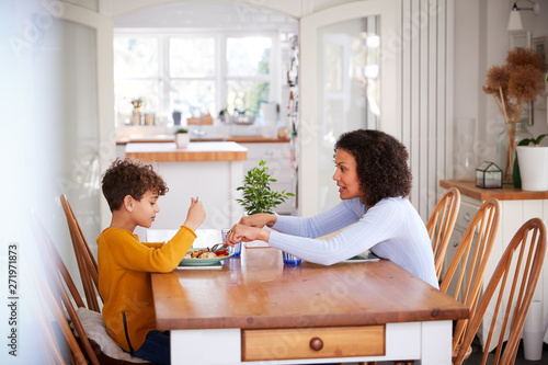 Fotografía  Single Mother Sitting At Table Eating Meal With Son In Kitchen At Home