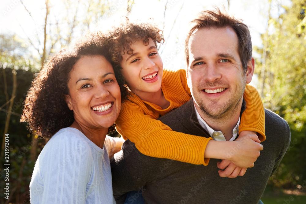 Fototapeta Outdoor Portrait Of Smiling Family In Garden At Home Against Flaring Sun