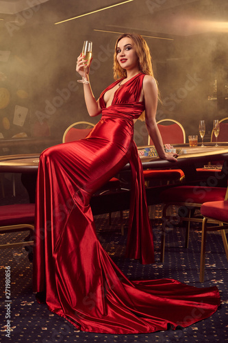 Photo  Young beautiful woman is posing against a poker table in luxury casino