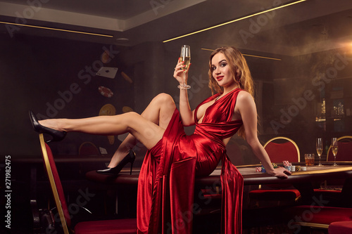 Young beautiful woman is posing against a poker table in luxury casino. - 271982475