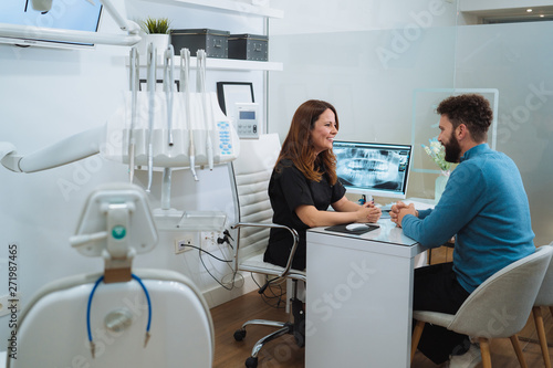 Fototapety, obrazy: Female dentist showing x-ray footage of teeth to male patient in clinic