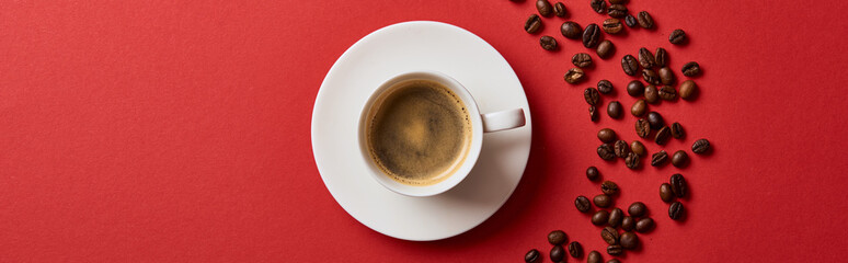 top view of delicious coffee in cup near roasted beans on red background, panoramic shot