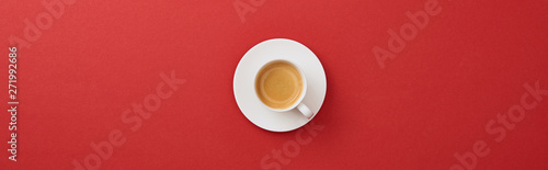 Obraz top view of white cup with fresh coffee on saucer on red background, panoramic shot - fototapety do salonu