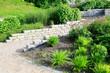 canvas print picture - Moderner Garten- und Landschaftsbau: Gehweg und Mauern aus Natursteinen mit integrierten Sitzbänken und Anpflanzungen