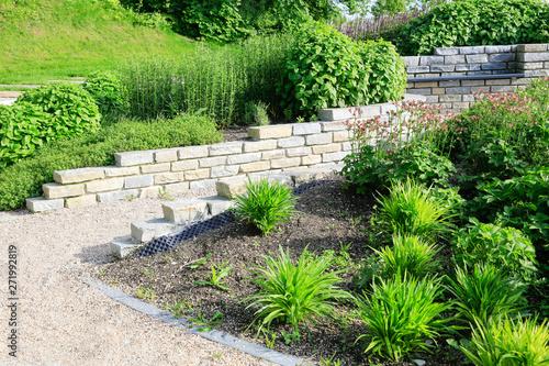 Poster Vegetal Moderner Garten- und Landschaftsbau: Gehweg und Mauern aus Natursteinen mit integrierten Sitzbänken und Anpflanzungen