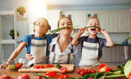 Fototapeta mother with children preparing vegetable salad obraz